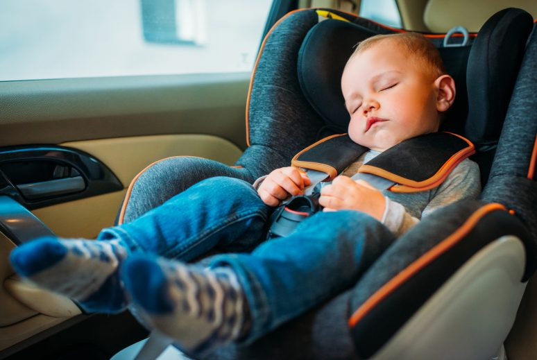 cute little baby sleeping in child safety seat in car
